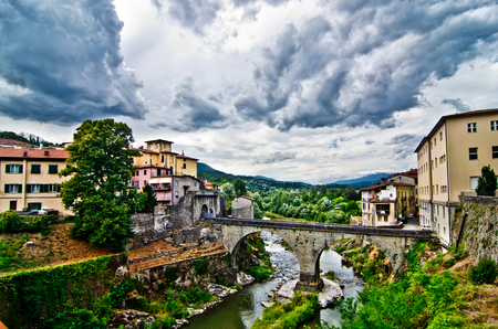 stone bridge connects two opposite banks of a river that flows into an ancient village under a stormy sky laden with clouds of rain