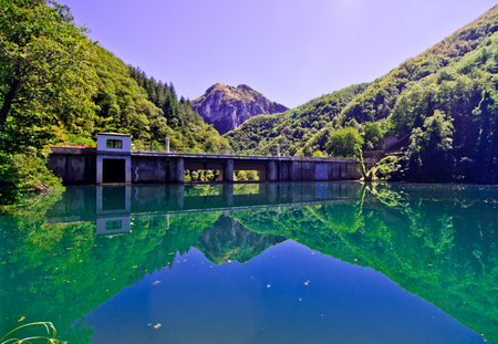dam with blue and green water forms a small lake in the midst of mountains covered by dense forests Stock Photo