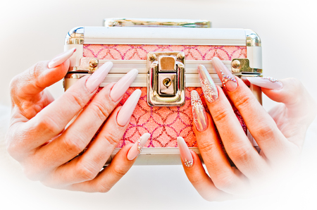 hands with nails decorated with snowflakes and glitter bring the box of secrets as a gift Banco de Imagens