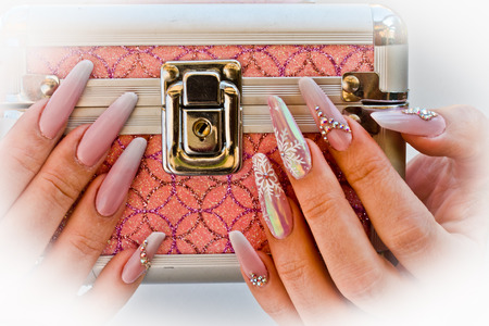 hands with nails decorated with snowflakes and glitter bring the box of secrets as a gift Stockfoto