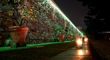 lighted candles mark the path in the garden along an ancient stone wall