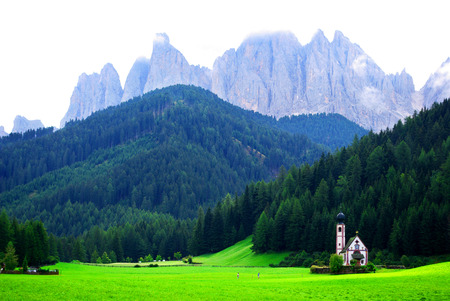 green meadow with small white church under the rocky mountains of the dolomites and the cloudy sky Stock Photo