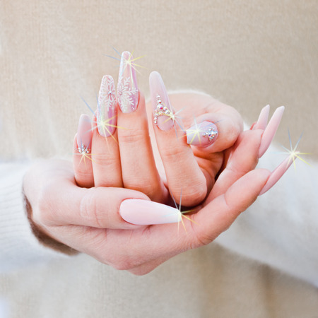 nails with pink, white and brilliant decorations that form light reflections Stock Photo