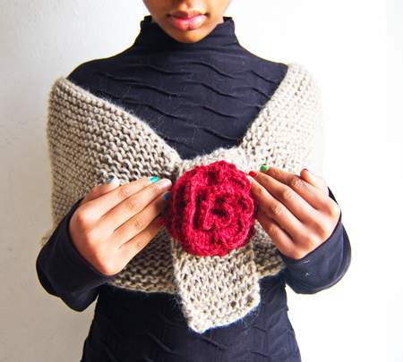 African American girl wrapped in soft woolen scarf with red rose