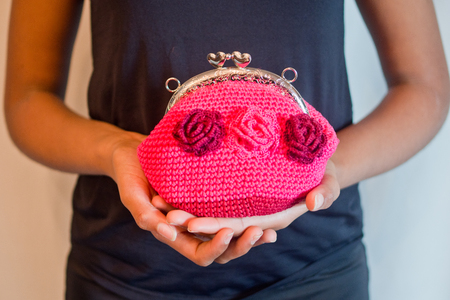 Handmade crochet bag with bright pink cotton thread with three fuchsia flowers held on the hand