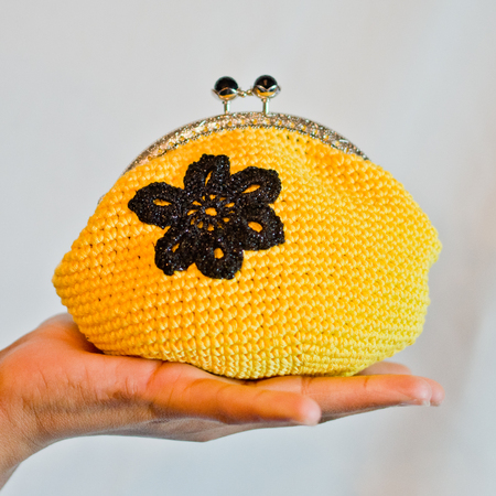 young hand holds small yellow purse with black flower crocheted