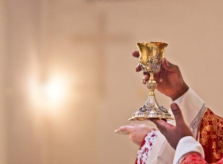 manos del sacerdote levantan la copa que contiene la sangre de Cristo, el sagrado grial Foto de archivo