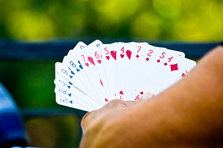 hand holding playing cards while playing for fun or for money with green background Stock Photo