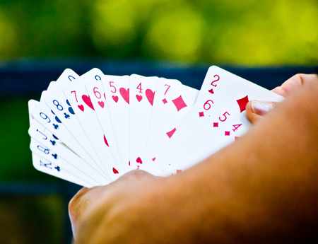 hand holding playing cards while playing for fun or for money with green background Banque d'images