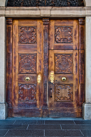 antique wooden door with knocker and burnished metal locking mechanism