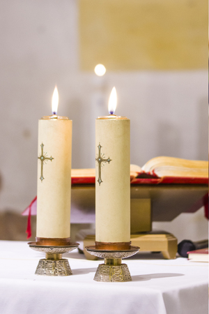 two candles with a cross light illuminate the church's atre with the blessed gospel, water and wine ready for holy mass 스톡 콘텐츠