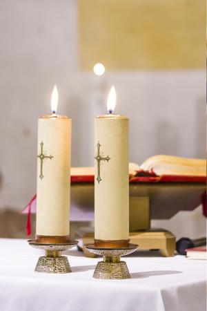 Zwei Kerzen mit einem Kreuzlicht erleuchten das Kirchenat mit dem gesegneten Evangelium, Wasser und Wein, die für die heilige Messe bereit sind Standard-Bild