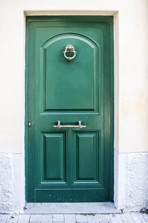 Puerta de madera verde desgastada por el uso del edificio histórico. Foto de archivo