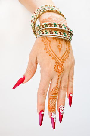 hand with henna tattoo, nails decorated with brilliants and bracelets with precious stones