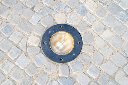 floor with small stone tiles, cement mortar and luminous lamp to illuminate the perimeter of parks or garde