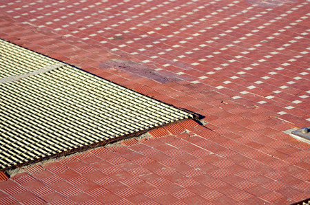 floor with small tiles in brick and stone, cement mortar and metal ventilation grating Stock Photo