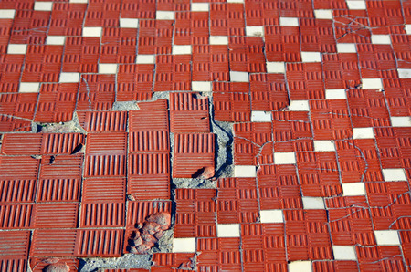 floor with small brick tiles and ceramic tiles with strong decay, breakage, small landslides Stock Photo