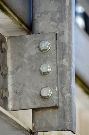 metal building: detail of vertical structure joined with bolts to the horizontal beam Stock Photo