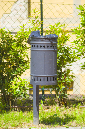 in the garden is a metal waste basket decorated with small circles Stock Photo