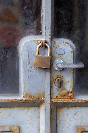 old padlock closes rusty metal door with glass windows