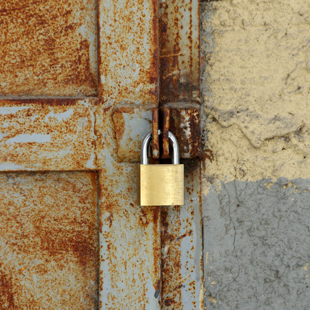 new padlock closes old rusty metal door with glass windows