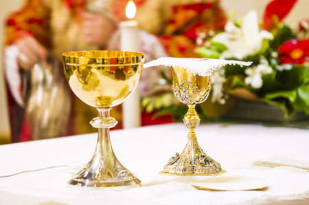 goblet with wine, blood of christ, and pyx with host, body of christ, ready on the altar of holy mass