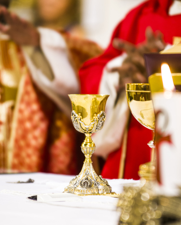 consecration of the holy mass: the wine becomes blood of christ and the host becomes the body of christ on the altar