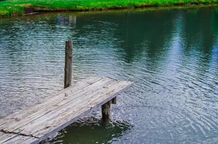 old wooden pier on the lake with fresh and clean mountain spring water Stock Photo