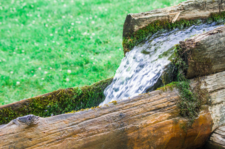 water source of life flows fresh and clean from the mountain to the valley in a wooden channel in nature Imagens