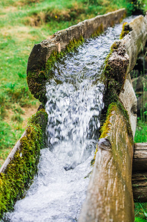 water source of life flows fresh and clean from the mountain to the valley in a wooden channel in nature Stock Photo