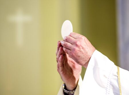 during the celebration of the Mass the hands of the priest, like the hands priest consecrate the host which becomes the body of Christ Stock Photo