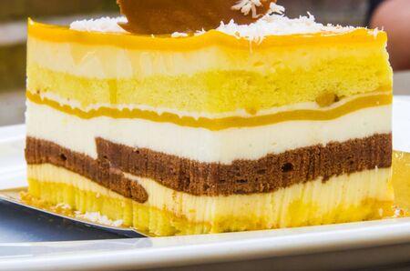 chocolate parfait, sponge cake, cream and mango with a milk chocolate hedgehog decoration