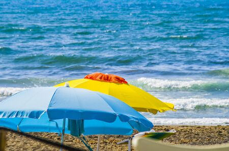 yellow and white and blue umbrellas with the blue sea in the background, three colors symbols of summer like paintings