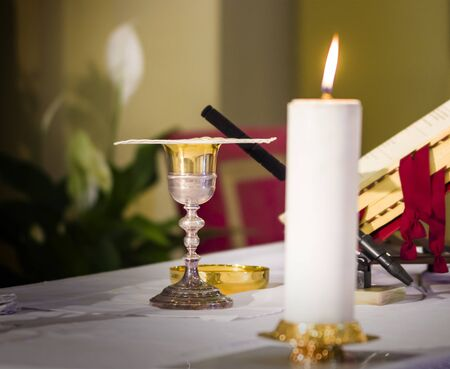 in the church the lit candle illuminates the wine, blood of christ, and the host, the body of christ for the communion of the faithful Stock Photo