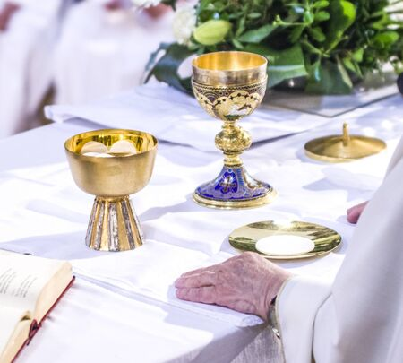 hand of the pope with consecrated host that becomes the body of jesus christ and chalice for wine, blood of christ, in the churches of rome and all over the world