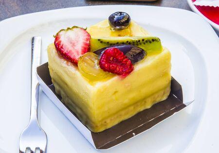 cake, passion fruit semifreddo cube with strawberry, kiwi, grapes, plum, blackberry and cape gooseberries