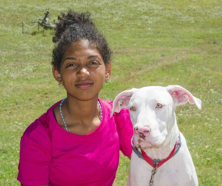 Young Brazilian dog trainer with beautiful white dog with big yellow eyes