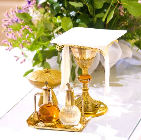 chalice for wine, blood of christ, and ciborium with host, body of christ, and ampoules with wine and water for the consecration on the others of the churches for pope francesco Archivio Fotografico