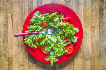 Healthy tomatoes and lamb's lettuce salad, seasoned with oil, salt, pepper, vinegar and lemon juice, served on a red plate on a wooden table worn by time and use.