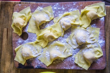 Italian housewife prepares egg pasta, stuffed tortelli on a pastry board, ready for the party lunch.