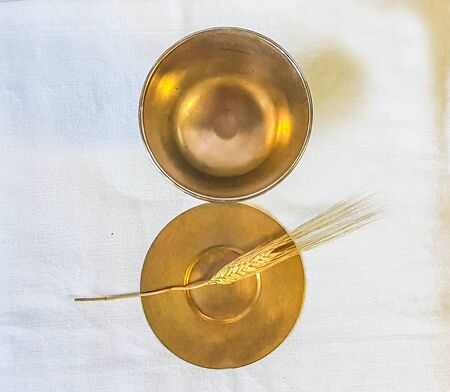ear of wheat ripens for bread which becomes the body of jesus christ and chalice to receive wine, the blood of christ, for the mass of the faithful.