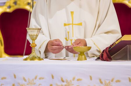 hand of the pope with consecrated host that becomes the body of jesus christ and chalice for wine, blood of christ, in the churches of rome and all over the world 免版税图像