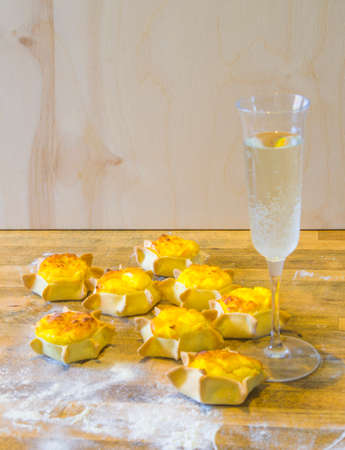 glass of iced sparkling wine with star-shaped sweets with shortcrust pastry, ricotta and cream