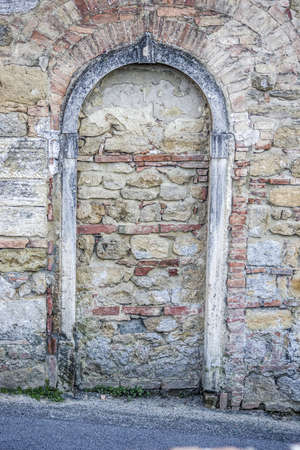ancient arch of the stone gate in the medieval walls of the historic city