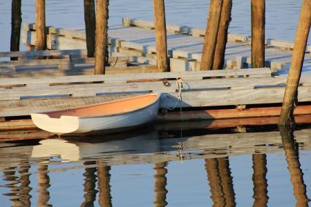 skiff: Lone skiff floating alongside a dock Stock Photo