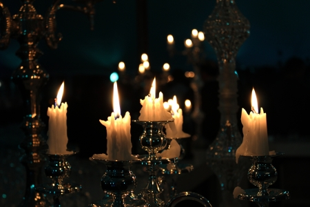 Candles burning at night on highly polished Candlestick Holders