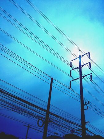 wire: The sun behind power line post