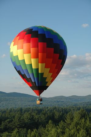 Hot air balloon soaring above the treetops Imagens