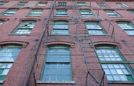 Rows of windows and fire escape in brick wall of old factory building Imagens