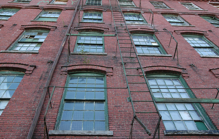 abandoned factory: Rows of windows and fire escape in old factory building Stock Photo